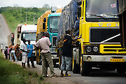 Drivers wait outside their trucks as they line up on the roadside at a deviation near Notse, Togo on Thursday October 2, 2008.