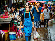 08 JUNE 2017 - BANGKOK, THAILAND: Shoppers and workers walk through Khlong Toey Market, Bangkok's main fresh market. Thai consumer confidence dropped for the first time in six months in May following a pair of bombings in Bangkok, low commodity prices paid to farmers and a sharp rise in the value of the Thai Baht versus the US Dollar and the EU Euro. The Baht is surging because of political uncertainty, related to Donald Trump, in the US and Europe. The Baht's rise is being blamed for a drop in Thai exports. This week the Baht has been trading at around 33.90 Baht to $1US, it's highest point in two years.      PHOTO BY JACK KURTZ