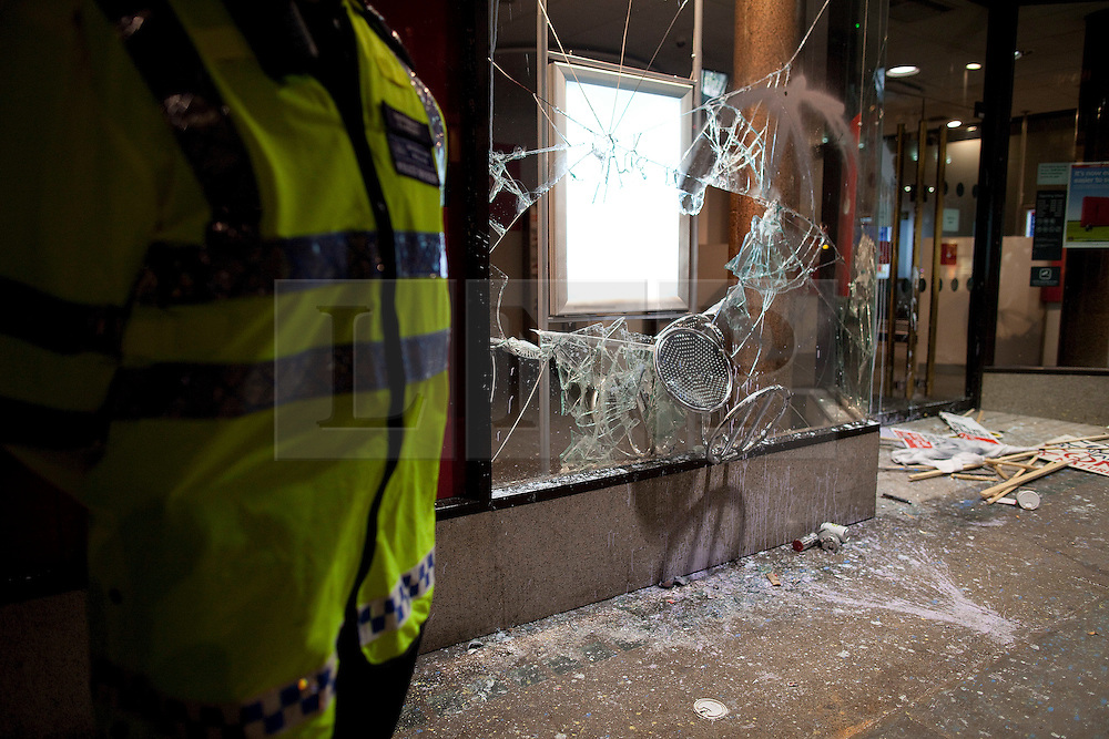 "© under license to London News Pictures. 25/03/2011: Following large anticuts protests across central London, a policeman stands guard outside a branch of Santander, which had its windows smashed by protesters. Credit should read ""Joel Goodman/London News Pictures""."