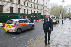 © Licensed to London News Pictures. 07/04/2014. London, UK. David Davies MP passes the scene. Armed Police arrest a man in King Charles Street today 7th April 2014. The street that runs between the Foreign Office and The Treasury, including an entrance to Downing Street has a search point at it's entrance. The man was led away to a waiting police van and officers were seen collecting evidence and an Adidas bag. . Photo credit : Stephen Simpson/LNP