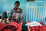 A mother  watches over her twin sons who are being re-hydrated with intravenous fluids on a paediatric ward at a cholera treatment Centre in Harare...Children and adults are treated at Beatrice Road Infectious Diseases Clinic in Harare, Zimbabwe...The clinic is staffed by locals but assisted by MSF.
