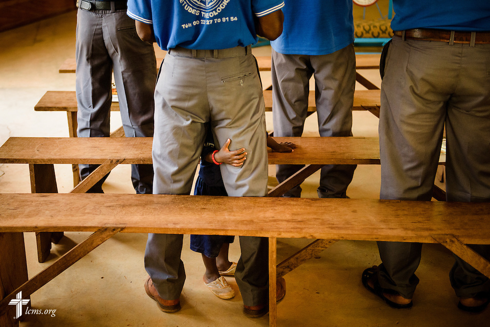 A young boy clutches his father during Vespers at the Lutheran Center for Theological Studies (CLET) on Tuesday, Feb. 14, 2017, in Dapaong, Togo. Families from Francophone African countries bring their families with them while they are studying in the program. LCMS Communications/Erik M. Lunsford