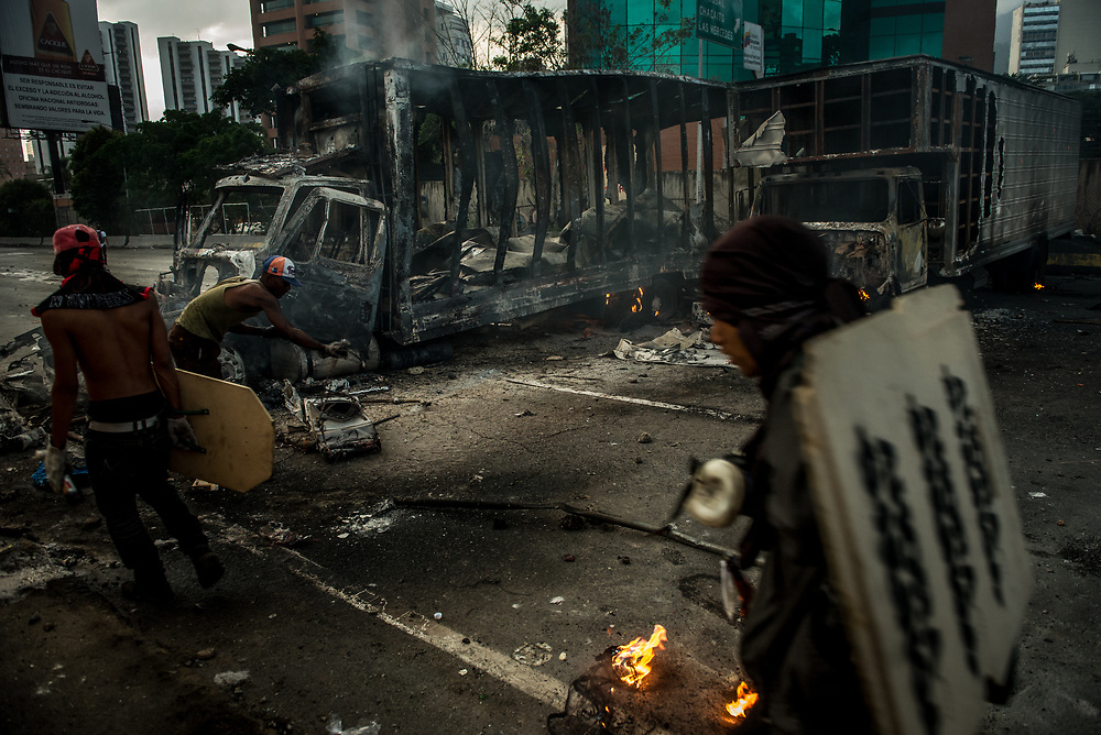 "CARACAS, VENEZUELA - MAY 27, 2017:  Anti-government protesters of ""The Resistance"" use two industrial sized trucks that they highjacked and burned as road blocks to shut down the main highway that runs through Caracas. The streets of Caracas and other cities across Venezuela have been filled with tens of thousands of demonstrators for nearly 100 days of massive protests, held since April 1st. Protesters are enraged at the government for becoming an increasingly repressive, authoritarian regime that has delayed elections, used armed government loyalist to threaten dissidents, called for the Constitution to be re-written to favor them, jailed and tortured protesters and members of the political opposition, and whose corruption and failed economic policy has caused the current economic crisis that has led to widespread food and medicine shortages across the country.  Independent local media report nearly 100 people have been killed during protests and protest-related riots and looting.  The government currently only officially reports 75 deaths.  Over 2,000 people have been injured, and over 3,000 protesters have been detained by authorities.  PHOTO: Meridith Kohut"