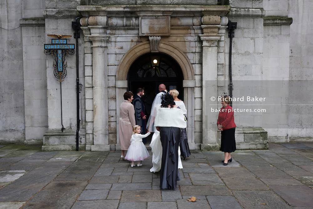 A bride and wedding guests including a young, interested bridesmaid file into the RAF church before the ceremony.