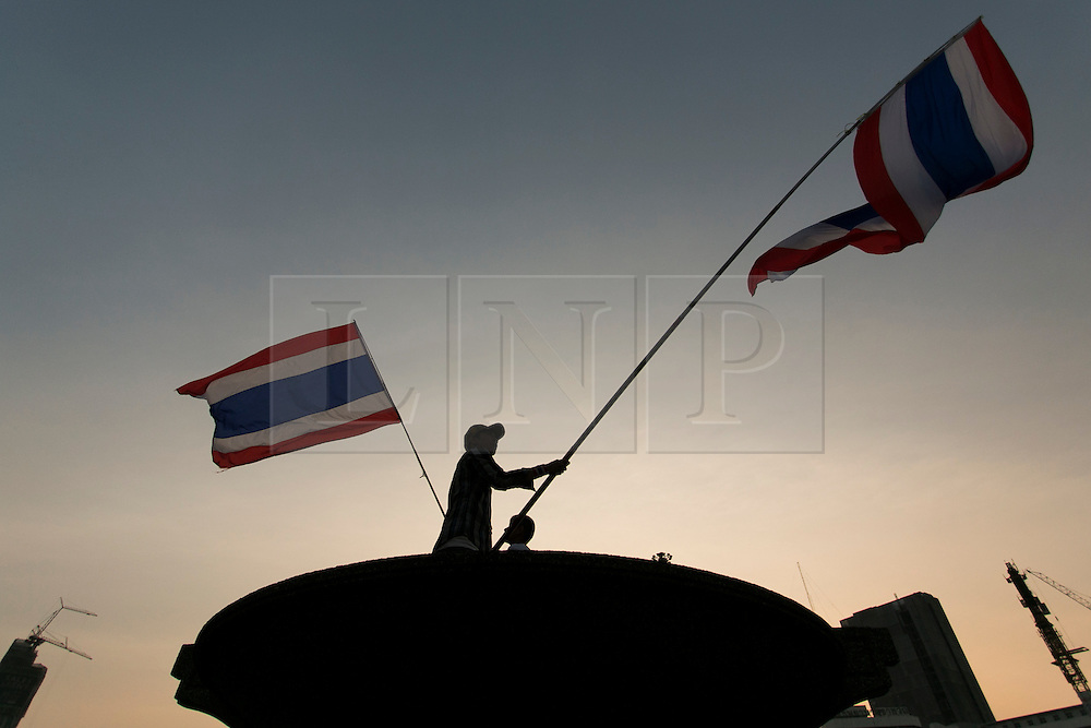 © Licensed to London News Pictures. 16/01/2014. An Anti Government silhouetted protestor waves the thai flag at a Rally during the fourth day of the 'Bangkok Shutdown' as anti-government protesters continue with their 'shutdown' of Bangkok.  Major intersections in the heart of the city have been blocked in their campaign to oust Prime Minister Yingluck Shinawatra and her government in Bangkok, Thailand. Photo credit : Asanka Brendon Ratnayake/LNP