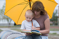 Young boy and woman sit under yellow umbrella reading a book