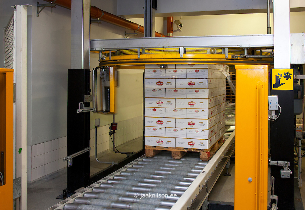Distribution warehouse with rolling belt, rollers, stacks of beer in cardboard boxes, shrinkwrapped on pallets. End of the production line. Machinery and lifting gear. Shrinkwrapping machinery.