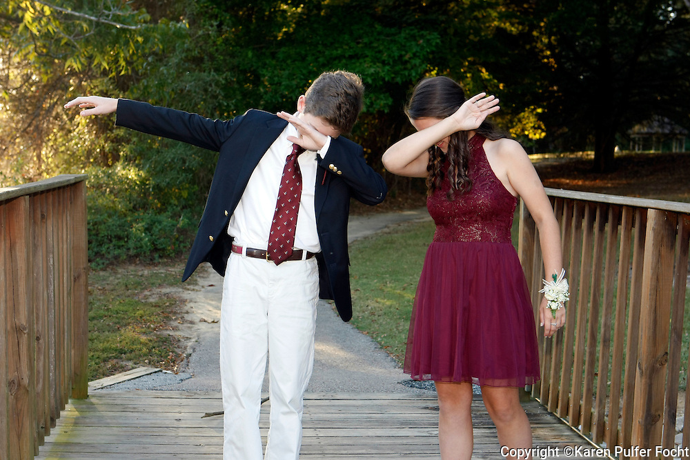 """Teens """"dabbing."""" Dabbing is a popular dance in 2016. They practice before going to homecoming dance."""