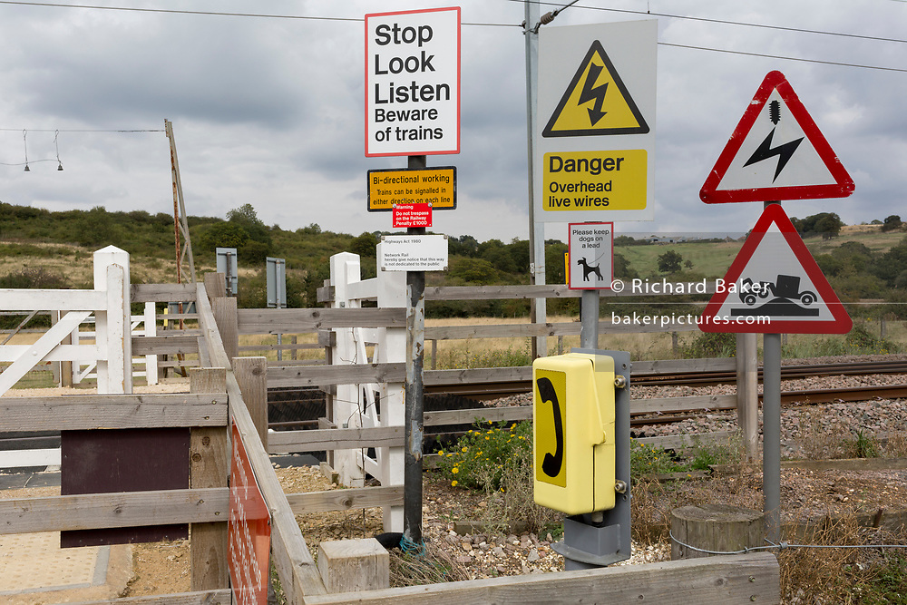 A landscape of a Network Rail railway crossing consisting of warning signs that tell crossing pedestrians of the dangers of overhead electricity wires - and to listen and look for approaching trains whose route takes them across agricultural marshland near Hadleigh Castle, on 10th September 2019, in Leigh-on-Sea, Essex, England.