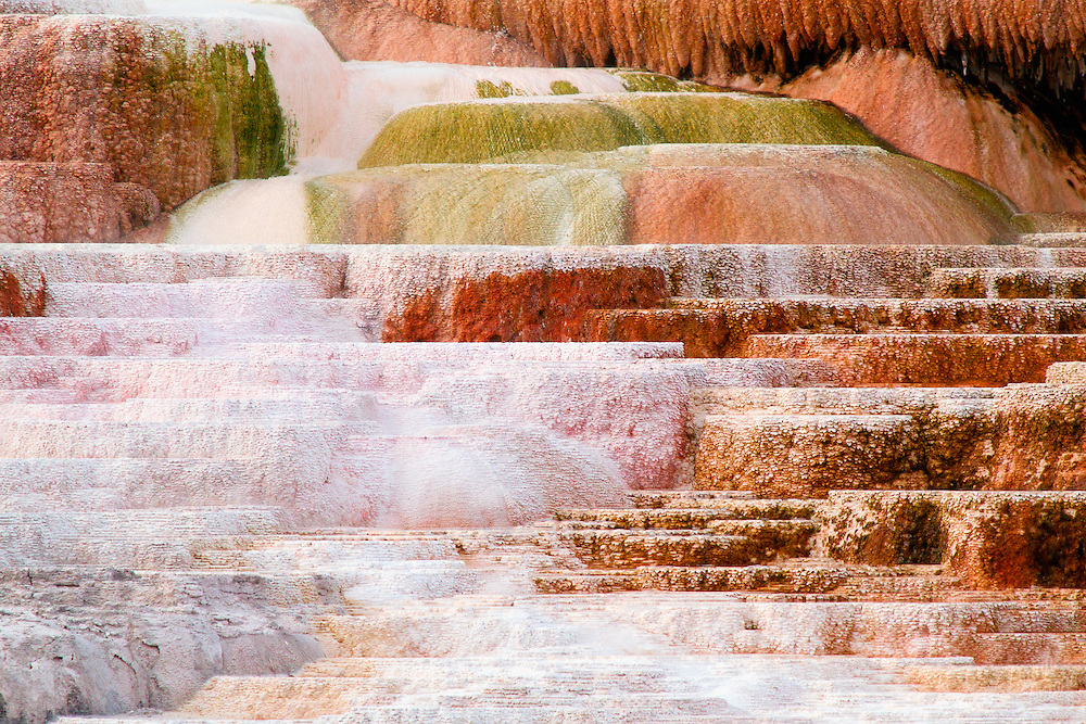 A little geothermal energy to push the water to the surface, and gravity to send it back downhill. Adjust for chemistry with calcification deposits to build the layers. Add the life of thermophiles to the mix and their photosynthetic pigments change color from the sun's rays. It's the beauty of science and the art of nature.