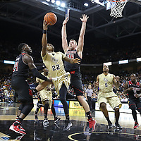 UCF Knights guard Brandon Goodwin (22) drives between Louisville Cardinals forward Montrezl Harrell (24) and Louisville Cardinals forward Stephan Van Treese (44) during an NCAA basketball game between the 14th ranked Louisville Cardinals and the UCF Knights at the CFE Arena on Tuesday, December 31, 2013 in Orlando, Florida. (AP Photo/Alex Menendez)