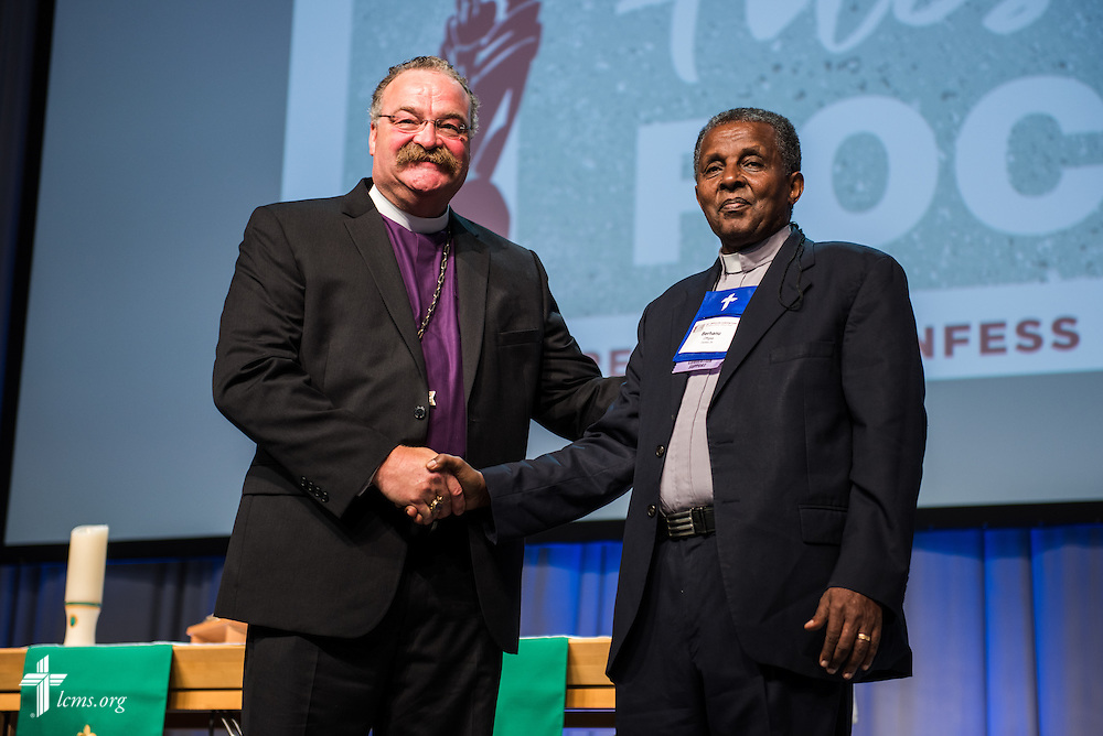 The Rev. Dr. Berhanu Ofgaa, general secretary of the Ethiopian Evangelical Church Mekane Yesus, is welcomed by the Rev. Dr. Matthew C. Harrison, president of the LCMS, during the 66th Regular Convention of the Lutheran Church—Missouri Synod on Wednesday, July 13. LCMS/Frank Kohn
