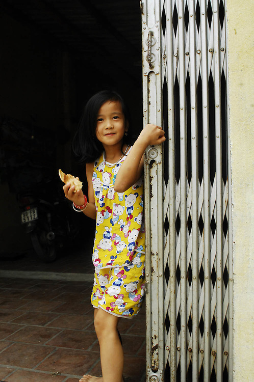 A young girl comes to the front door of her home to see the group of Americans walking through her neighborhood near Hanoi. (Laura Fong Torchia/Special to the Beacon Journal)