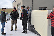 Three men talk while two men move a mattress at the parking lot of Worth a Second Look in Kitchener, Ontario, Canada. Most of the men are part of Job Cafe, a program of The Working Centre, either as management or as casual day workers.