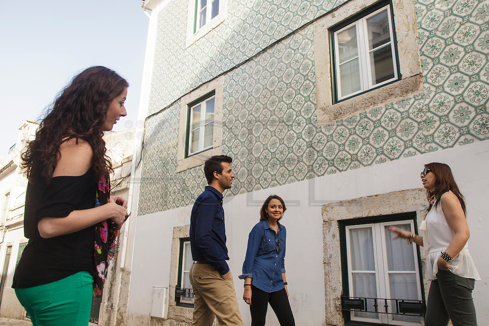 Friends near a facade decorated with ceramic tiles at Madragoa traditional Lisbon district.