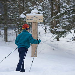 A young girl cross-country skis past a trail sign at the AMC's Little Lyford Pond Camps in Maine's Northern Forest.  Near Greenville.