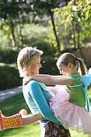 Mother holding up daughter wearing tutu in park side view