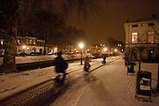 Fietsers in de avondsneeuw