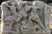 Sculpted detail from a marble sarcophagus showing figures fighting including one on horseback, at Ephesus, Izmir, Turkey. Ephesus was one of the most important centres in the ancient world for producing half-finished sarcophagi. They are of three types; garland, column or Attic. Many sarcophagi were found during the excavations of the area around Ephesus. In the necropolis are walled family tombs, monumental tombs, vauted tombs and sarcophagi within closed or open chambers. The sarcophagi were rectangular and were constructed of marble, stone, baked clay, or wood. Ephesus was an ancient Greek city founded in the 10th century BC, and later a major Roman city, on the Ionian coast near present day Selcuk. Picture by Manuel Cohen