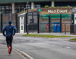 © Licensed to London News Pictures. 31/03/2020. London, UK. A man runs past the The All England Lawn Tennis Club, Wimbledon. AELTC is set to announce on Wednesday (1 April) the cancellation of the Wimbledon Tennis Championships 2020 due to the coronavirus pandemic. The pandemic has led to the cancellation of major sporting events across the World as the coronavirus crisis continues. Photo credit: Alex Lentati/LNP