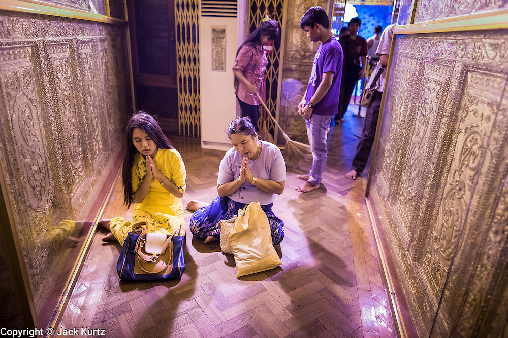 04 JUNE 2014 - YANGON, YANGON REGION, MYANMAR: People pray in Botataung Paya (Pagoda) in Yangon, Myanmar (Rangoon, Burma). Botataung is one of the most famous pagodas in Yangon with maze like interior of gold leaf covered walls. The pagoda houses a hair from the Buddha and is one of the most sacred sites in Burma. Yangon, with a population of over five million, continues to be the country's largest city and the most important commercial center.     PHOTO BY JACK KURTZ