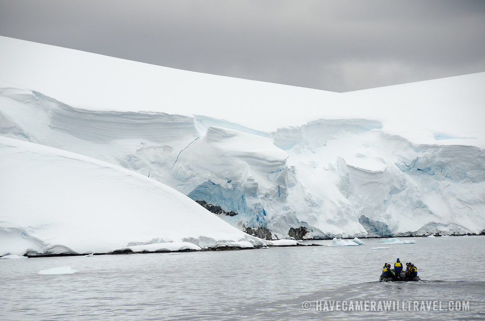 An inflatable zodiac with tourists heads toward the steep clifss of a glacier slowly falling into the sea at Melchior Islands on the western side of the Antarctic Peninsula.