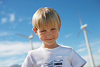 Boy (7-9) smiling at wind farm, portrait