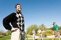 Golfer watching other golfer teeing off
