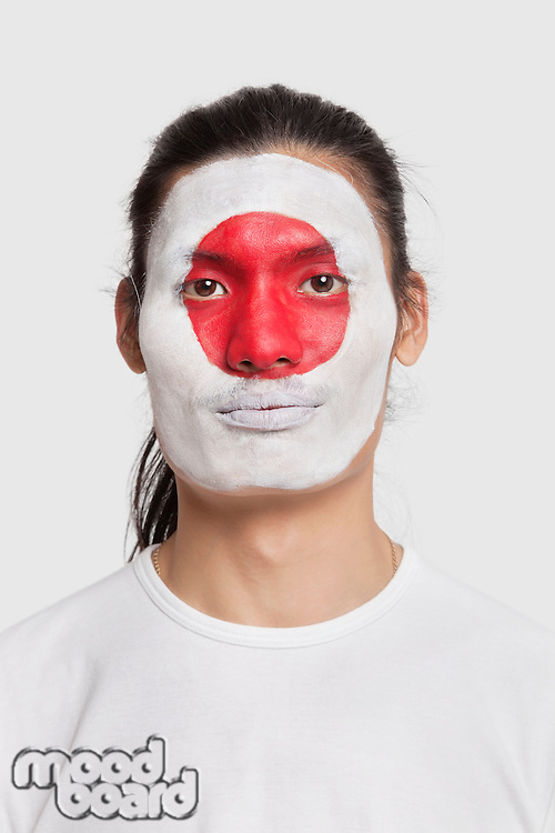 Portrait of young mixed race man with Japanese flag painted on face against white background