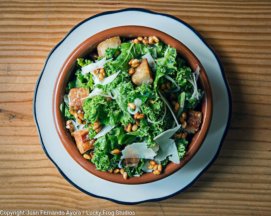 Krispy Porkbelly &amp; Kale Salad by Pubbelly<br /> - Preserved Lemon Vinaigrette<br /> - Parmesan Cheese<br /> - Candy Pine Nuts<br /> - Olive Oil &amp; Salt<br /> <br /> Photography by Juan Fernando Ayora / Lucky Frog Studios