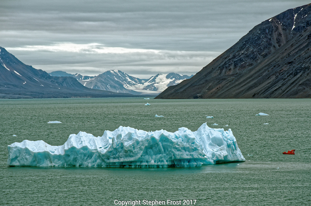 A lifeboat inspects an iceberg in the Arctic ocean off Svalbard.<br /> <br /> Svalbard, formerly known as Spitsbergen, is a Norwegian Archipelago in the Arctic Ocean.
