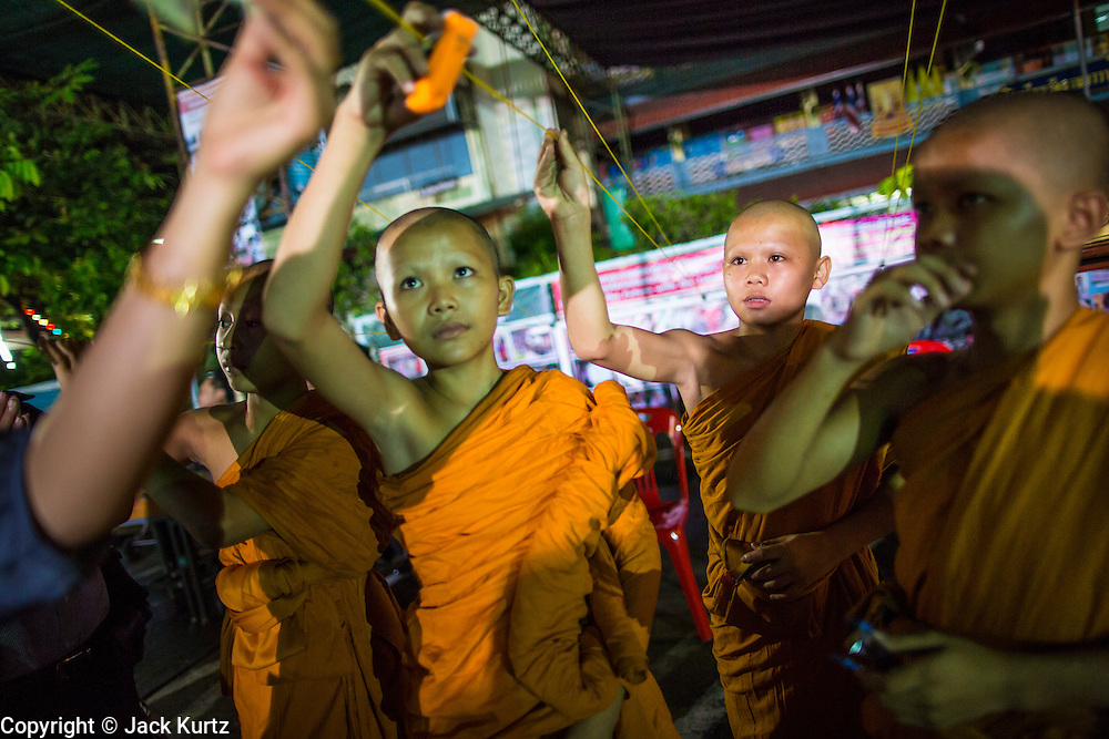 28 NOVEMBER 2012 - BANGKOK, THAILAND: Novice monks during Loy Krathong ceremonies at Wat Yannawa in Bangkok. Loy Krathong takes place on the evening of the full moon of the 12th month in the traditional Thai lunar calendar. In the western calendar this usually falls in November. Loy means 'to float', while krathong refers to the usually lotus-shaped container which floats on the water. Traditional krathongs are made of the layers of the trunk of a banana tree or a spider lily plant. Now, many people use krathongs of baked bread which disintegrate in the water and feed the fish. A krathong is decorated with elaborately folded banana leaves, incense sticks, and a candle. A small coin is sometimes included as an offering to the river spirits. On the night of the full moon, Thais launch their krathong on a river, canal or a pond, making a wish as they do so.    PHOTO BY JACK KURTZ