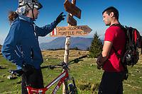 Mountain biker and hiker (Marius Berchi) at a wooden signpost for hiking trails in the Tarcu Mountains Natura 2000 site. Southern Carpathians, Munții Ṭarcu, Caraș-Severin, Romania.