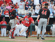 Mississippi's Sikes Orvis (24) scores behind Texas Tech's Hunter Redman (5) and Texas Tech's Ryan Moseley (44) at T.D. Ameritrade Park in the College World Series in Omaha, Neb. on Tuesday, June 17, 2014. Ole Miss won 2-1.