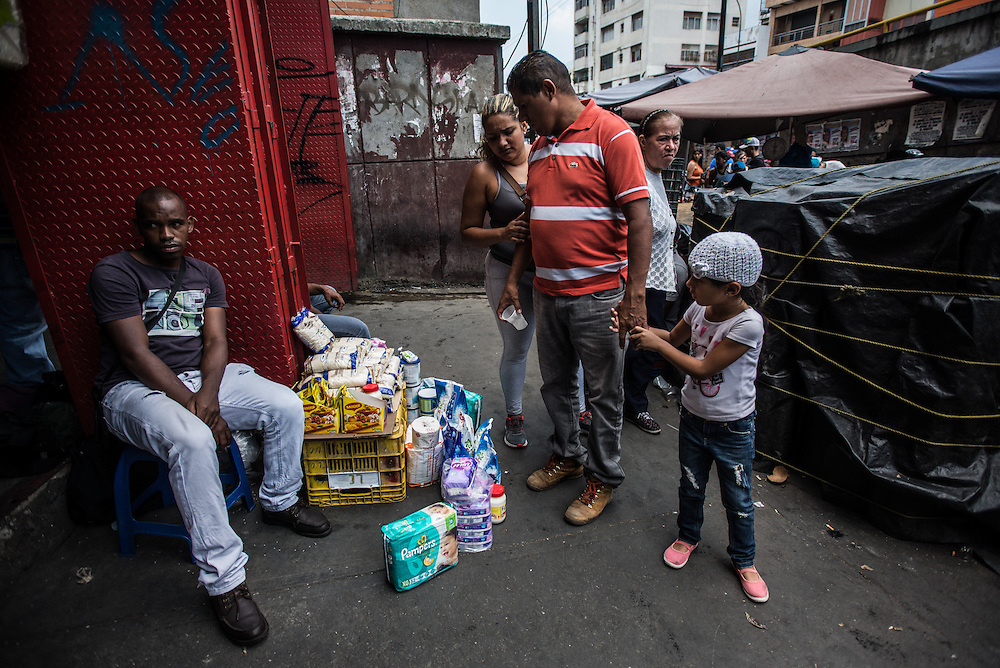 CARACAS, VENEZUELA - MARCH 22, 2016: Shoppers walk past goods for sale by &lsquo;bachaqueros&rsquo; - hustlers who buy hard-to-find price-controlled goods and re-sell them on the black market at exponentially higher prices.  These bachaqueros in the Petare slum in eastern Caracas were selling Pampers brand diapers for 2,000 bolivares for packs of 32 (the government regulated price is 154.80 bolivares) and birth control pills for 1,500 bolivares (the government price is 156,34 bolivares).  <br /> PHOTO: Meridith Kohut for IRIN News