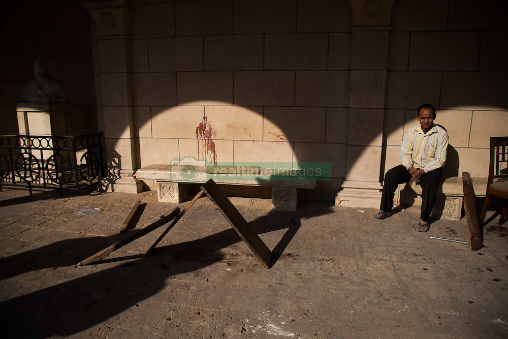 December 11, 2016 - Cairo, Egypt - Egyptian men sit at the scene of a bomb explosion that targeted the Saint Peter and Saint Paul Coptic Orthodox Church on December 11, 2016, in Cairo's Abbasiya neighbourhood. The blast killed at least 25 worshippers during Sunday mass inside the Cairo church near the seat of the Coptic pope who heads Egypt's Christian minority, state media said. (Credit Image: © Fayed El-Geziry/NurPhoto via ZUMA Press)