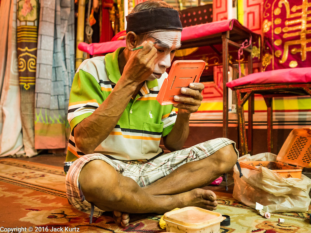 04 OCTOBER 2016 - BANGKOK, THAILAND:  A Chinese opera performer puts on his makeup on the stage at the Vegetarian Festival at the Chit Sia Ma Chinese shrine in Bangkok. The Vegetarian Festival is celebrated throughout Thailand. It is the Thai version of the The Nine Emperor Gods Festival, a nine-day Taoist celebration beginning on the eve of 9th lunar month of the Chinese calendar. During a period of nine days, those who are participating in the festival dress all in white and abstain from eating meat, poultry, seafood, and dairy products. Vendors and proprietors of restaurants indicate that vegetarian food is for sale by putting a yellow flag out with Thai characters for meatless written on it in red.    PHOTO BY JACK KURTZ