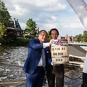 NLD/Amsterdam/20140612 - Hilton Haringparty 2014, general manager Roberto Prayer met de heer van As en het eerste vaatje hollandse nieuwe haring