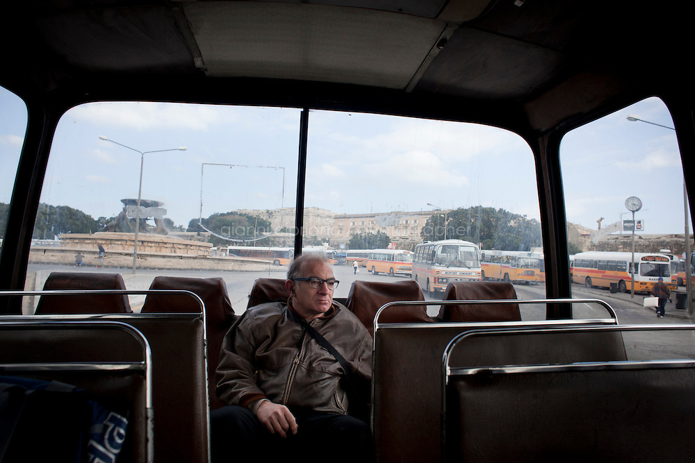 27 February 2011. Valletta, Malta. A man sits in the back of the n.81 bus going from Valletta to Medina, a medieval town located in the centre of island, 8 miles from Valletta.<br /> These buses, some of which are 60 years old, will be replaced in the following months by newer buses. There are approximately 500 buses in public transit service in Malta. The drivers themselves own most of the buses, but operate to a unified timetable set by the transport authority.<br /> <br /> &copy;2011 Gianni Cipriano<br /> cell. +1 646 465 2168 (USA)<br /> cell. +39 328 567 7923<br /> gianni@giannicipriano.com<br /> www.giannicipriano.com