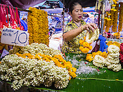 19 OCTOBER 2012 - BANGKOK, THAILAND:   A vendor displays marigold garlands in the Bangkok Flower Market. The Bangkok Flower Market (Pak Klong Talad) is the biggest wholesale and retail fresh flower market in Bangkok.  The market is busiest between 3:30AM and 6AM. Thais grow and use a lot of flowers. Some, like marigolds and lotus, are used for religious purposes. Others are purely ornamental.         PHOTO BY JACK KURTZ
