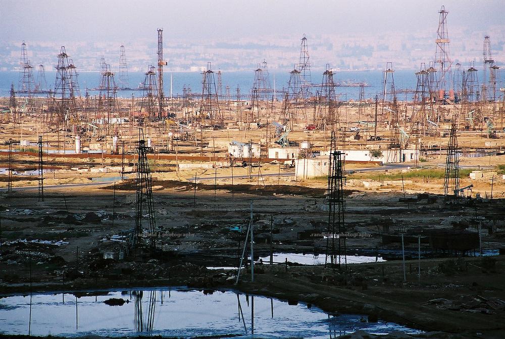 Der Schatten der untergehenden Sonne legt sich über das Selimkhanow-Ölfeld. Vor über 100 Jahren begann hier im Süden der aserbaidschanischen Hauptstadt Baku der erste Ölboom. Noch immer fördern hier Arbeiter Erdöl mit abenteuerlich alter Technik das schwarze Gold aus dem Untergrund. Überall rosten alte Bohrtürme vor sich hin, schwarze Seen aus Öl (vorne) verseuchen die Landschaft. Abwässer werden in das nahe gelegegen Kaspische Meer geleitet. Eine apokalyptische Landschaft. The old Selimkhanov oilfield near Baku, Aserbaijan.