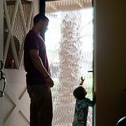 infant son reaching for doorknob to front door, dad watching