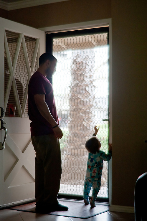 infant son reaching for doorknob to front door, dad watching