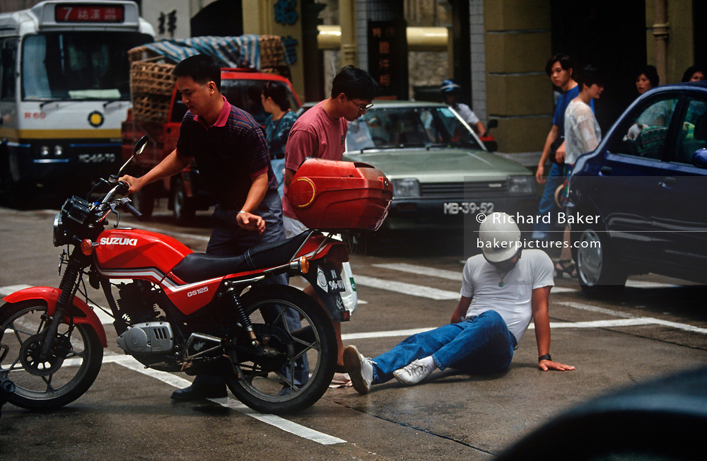 While still a Portuguese colony, a 1990s Macau motorbike rider picks himself up after a road traffic collision, on 10th August 1994, in Macau, China. (Photo by Richard Baker / In Pictures via Getty Images)