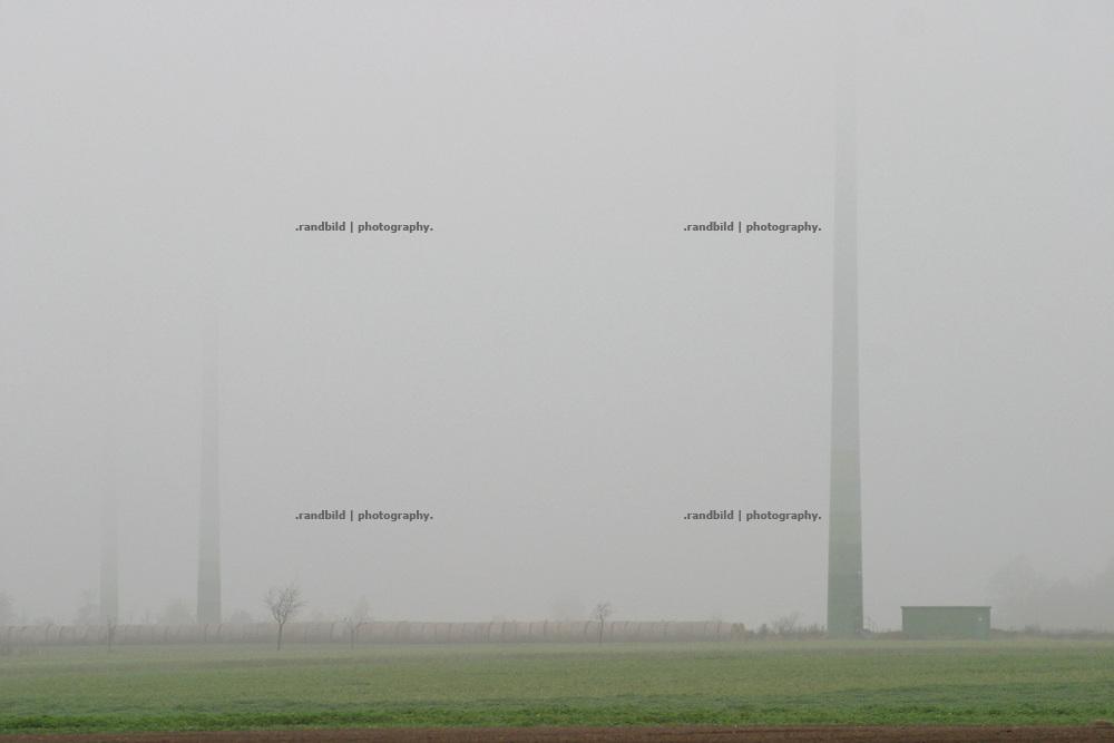 An einem nebligen Herbstmorgen verschwinden bei Clenze die Masten von drei Windrädern im Dunst...wind turbines hide by fog.