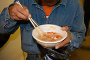 A homeless man eats soup provided by Volunteers from Groupo Esperanca a Brazilian and Nikkei Japanese catholic charity group at Hamamatsu station. Hamamatsu, Shizuoka, Japan. Saturday, March 21st 2009. Despite many Brazilian immigrants in Japan suffering badly in the economic crisis of 2008 and 2009, such charity groups provided food clothes and company to homeless immigrants and native japanese in Hamamatsu and other cities across Japan.