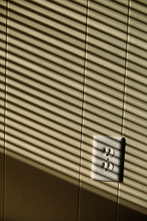 Striped shadows from blinds fall over an electrical socket in the wall.