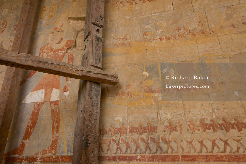 "A detail of wooden supports and ancient Egyptian hieroglyphs showing Somalian slaves at the Temple of Hatshepsut near the Valley of the Kings, Luxor, Nile Valley, Egypt. The Mortuary Temple of Queen Hatshepsut, the Djeser-Djeseru, is located beneath cliffs at Deir el Bahari (""the Northern Monastery""). The mortuary temple is dedicated to the sun god Amon-Ra and is considered one of the ""incomparable monuments of ancient Egypt."" The temple was the site of the massacre of 62 people, mostly tourists, by Islamists on 17 November 1997."