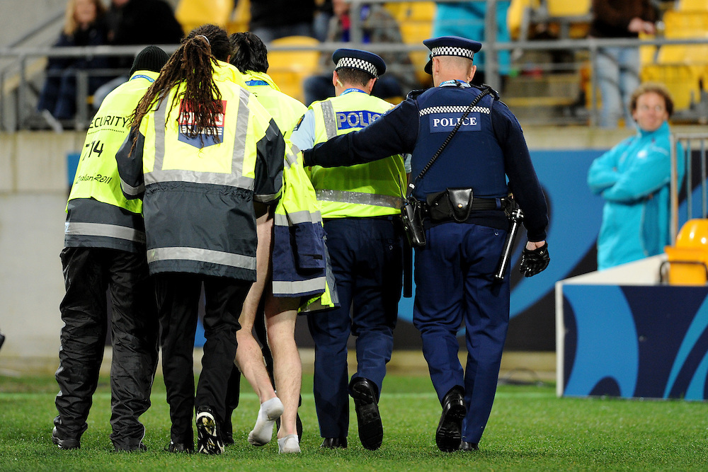 A streaker is escorted off the field during the Pool C, Australia v USA match at the IRB Rugby World Cup 2011. Wellington Regional Stadium, Wellington. Friday 23 September 2011...Photo: Mark Tantrum/photosport.co.nz..