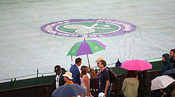Spectators shelter from the rain on day three of the Wimbledon Championships at the All England Lawn Tennis and Croquet Club, Wimbledon.